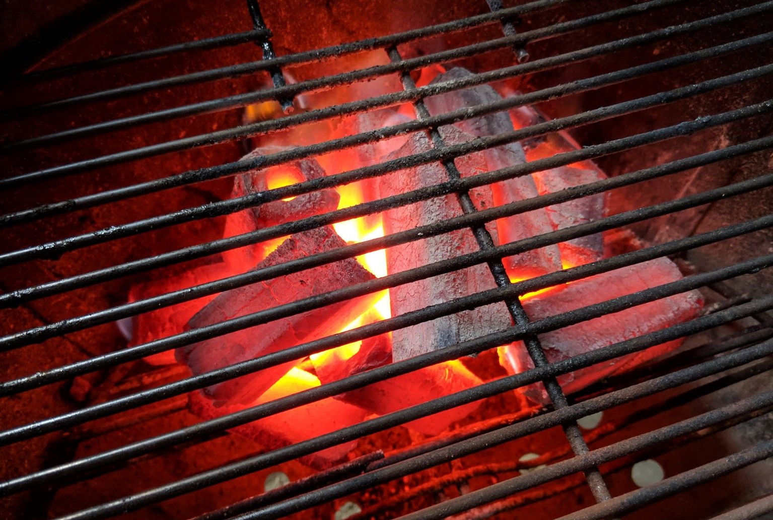 Image show long lasting glowing Hot White Charcoal Briquettes in a weber kettle