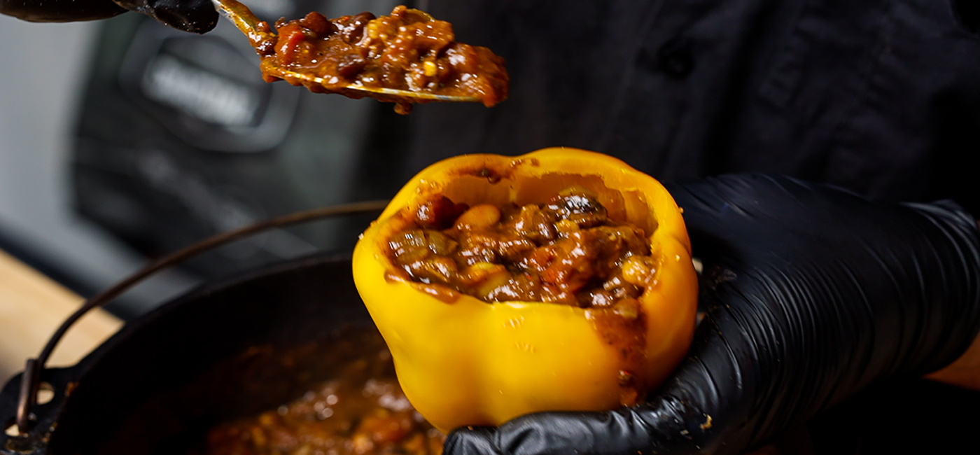 This images shows a man begin stuffing this chili into the capsciums